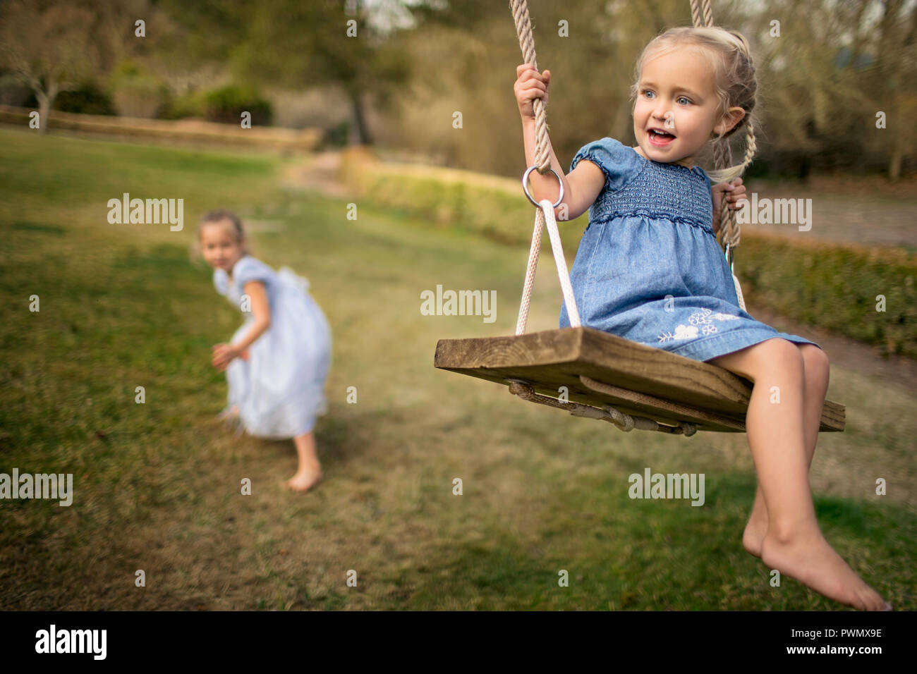 Two happy sisters playing on a swing in the garden. Stock Photo