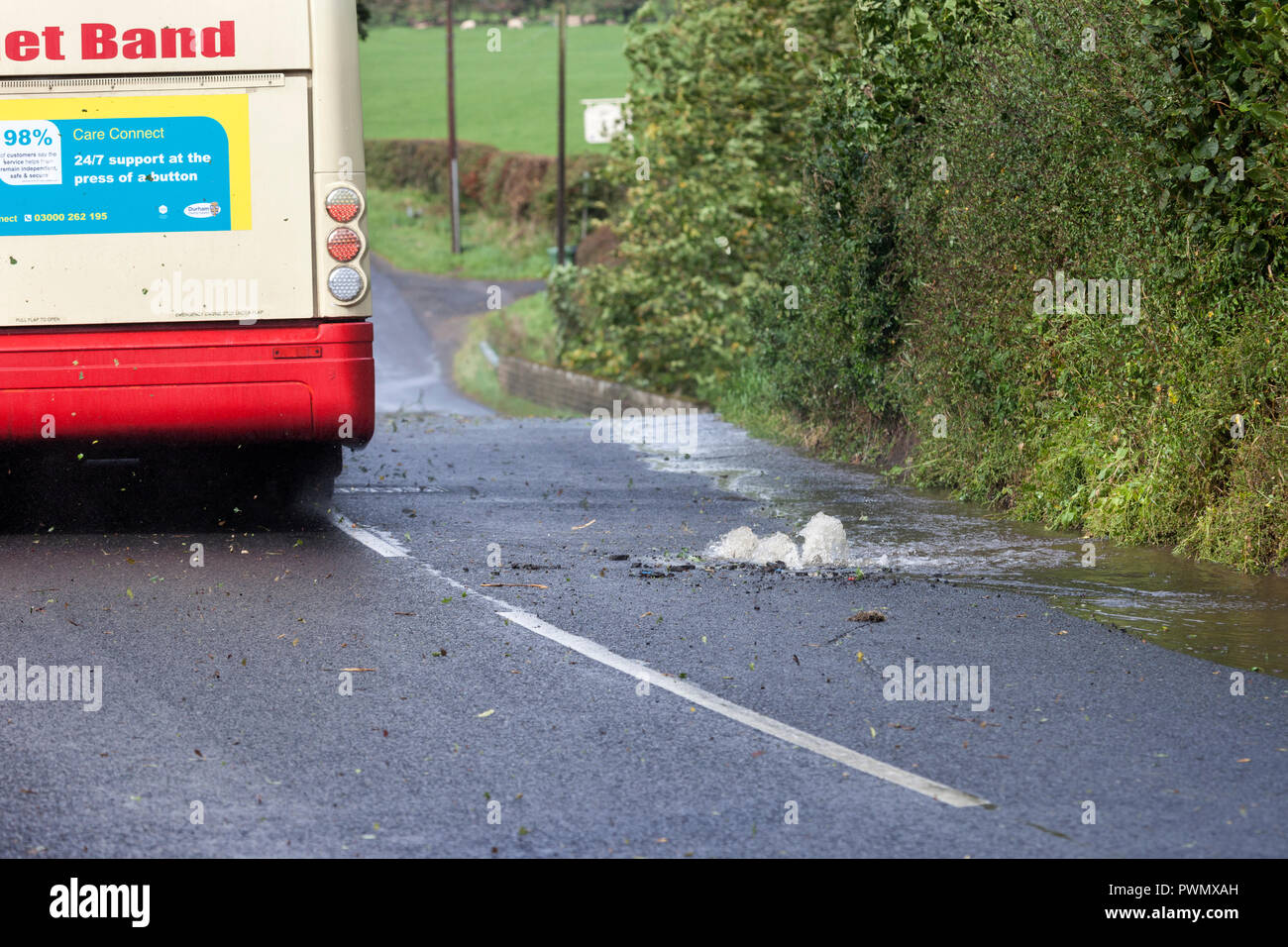 A Bus Driving Past a Burst Water Main in the Road, County Durham, UK - Stock Image
