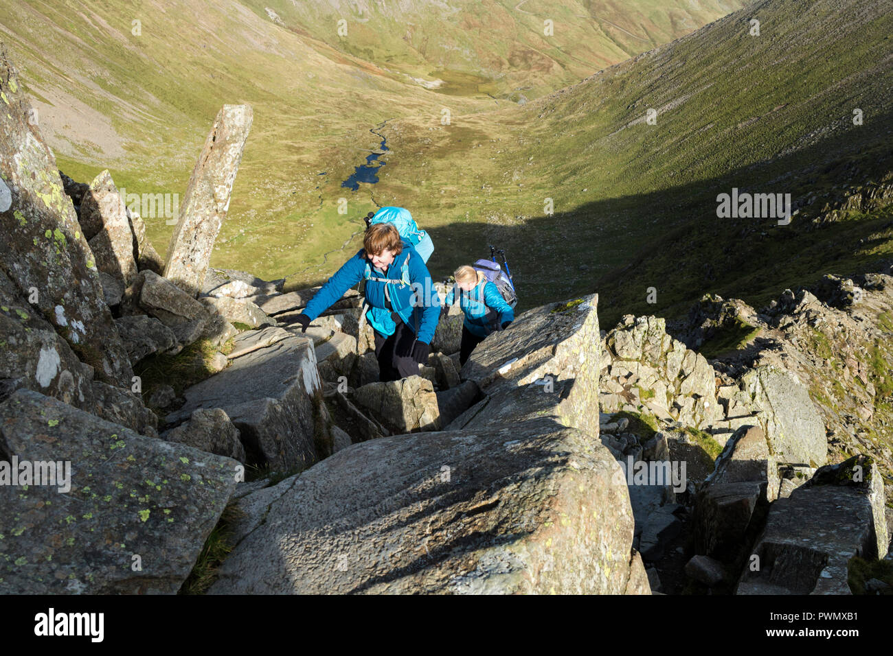 Two People Scrambling on Swirral Edge, Helvellyn, Lake District, Cumbria, UK. - Stock Image