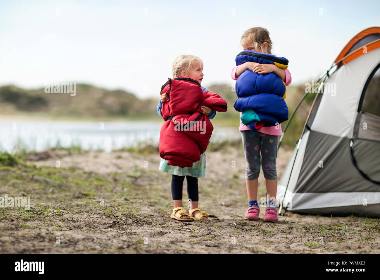 Two little girls are very excited to go camping. - Stock Image