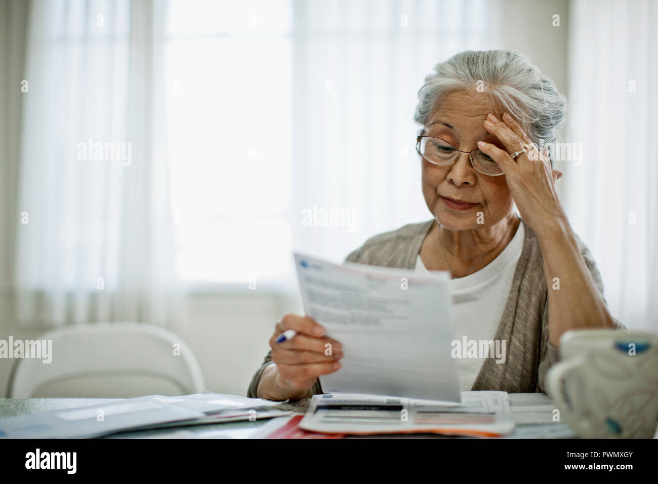 Anxious elderly woman is worried about how she can pay the bill she has received. - Stock Image