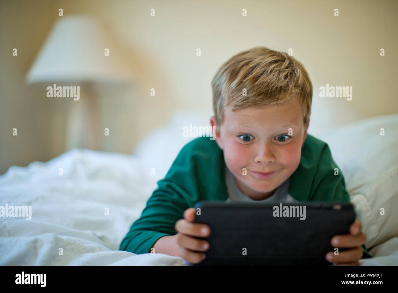 Young boy pulling a silly face while playing with a digital tablet. - Stock Image