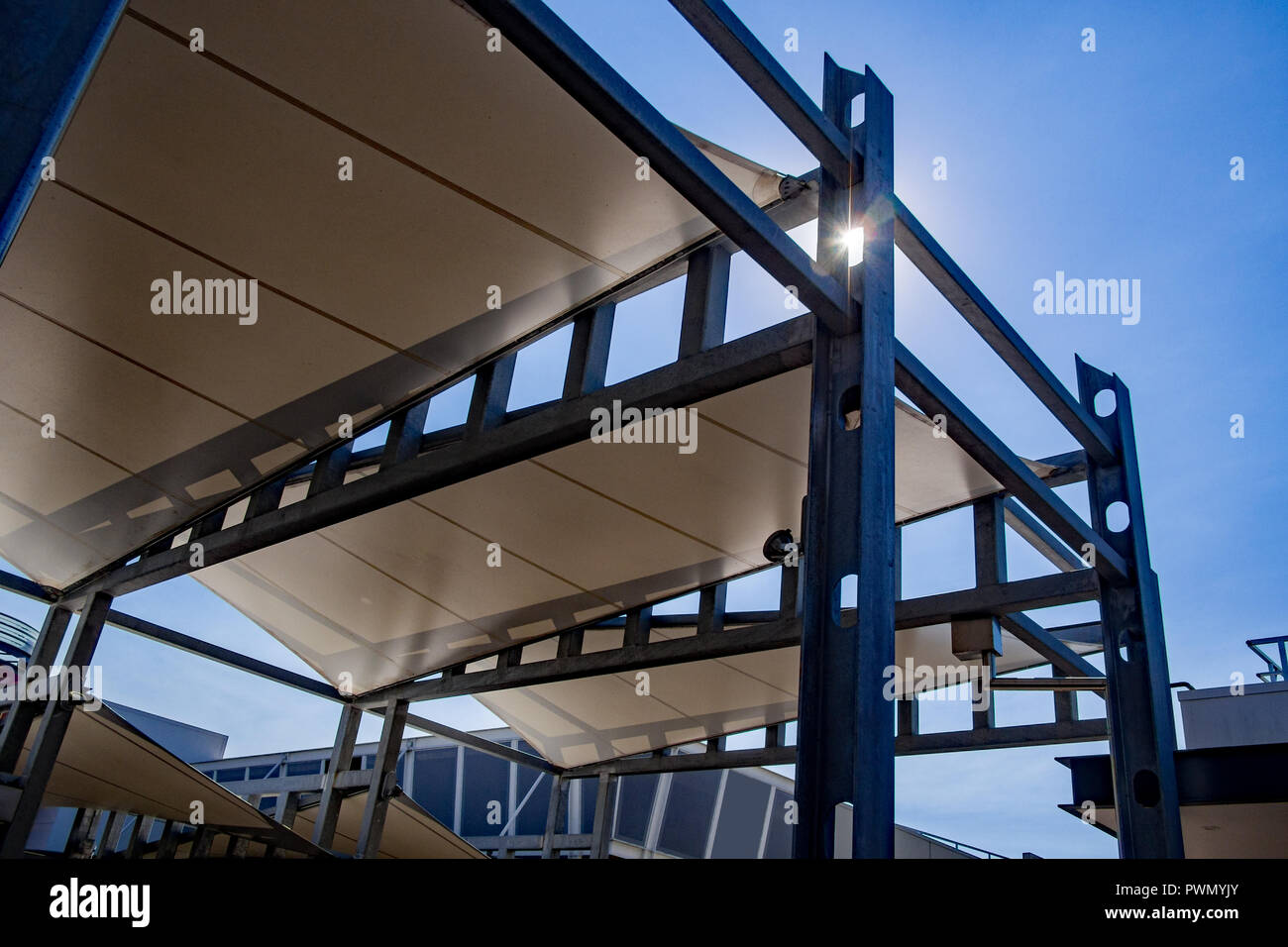 Sail shade pergola made of galvanized steel and white canvas tall standing strong structure against the blue sky Stock Photo