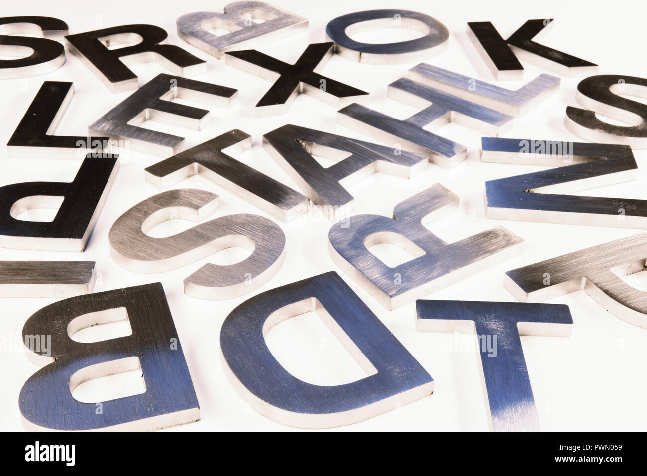 Shiny letters milled from metal lying on table. - Stock Image