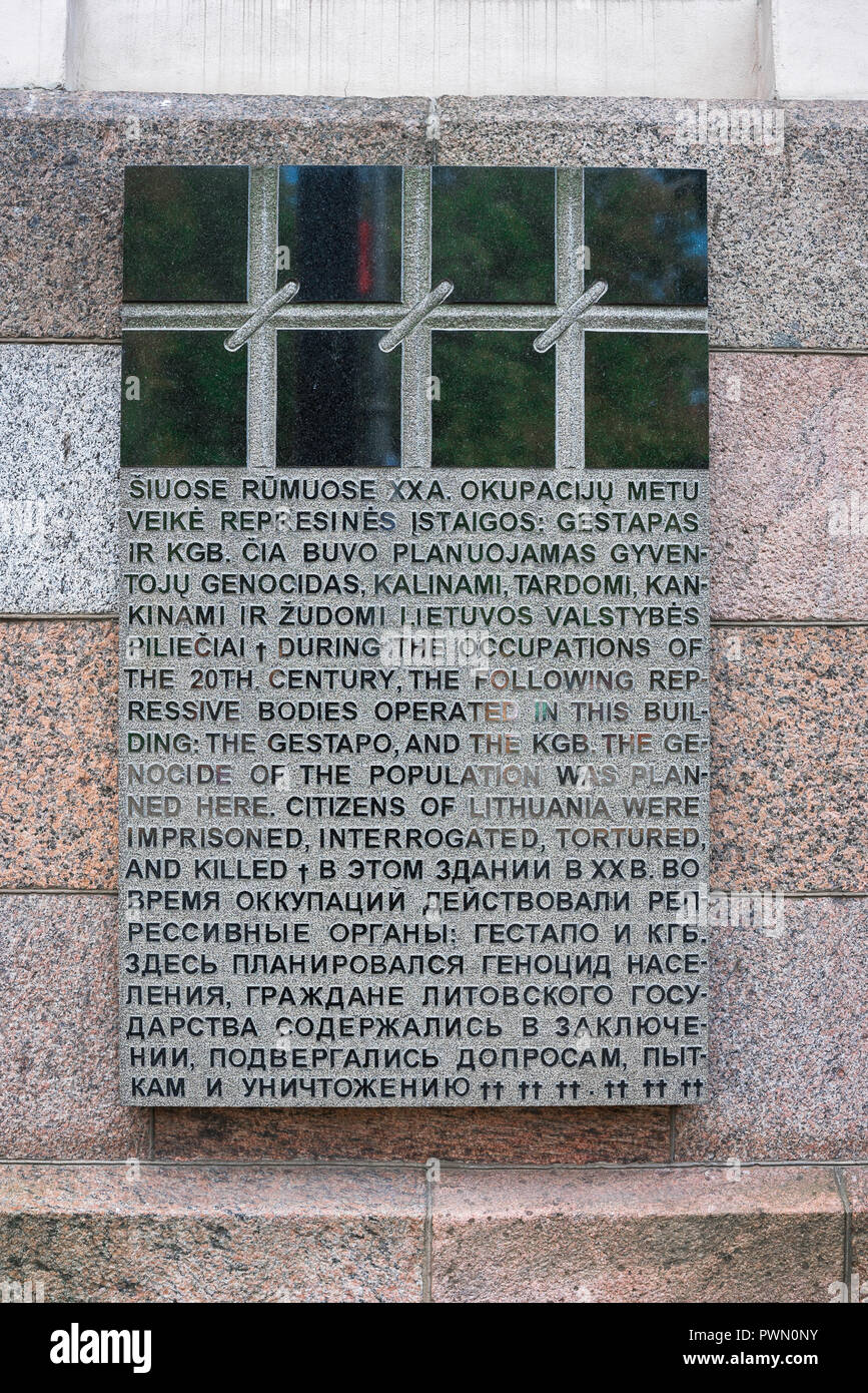 Granite plaque outside the Museum Of Genocide Victims in Vilnius informing visitors of the building's former purpose as a prison and torture chamber. - Stock Image