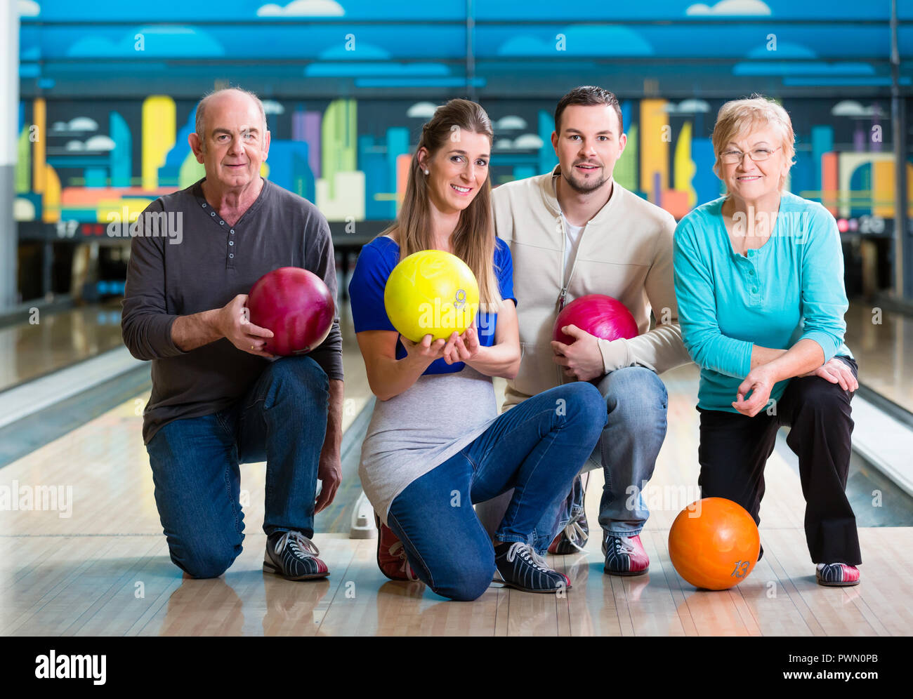 Family with multi colored bowling ball posing - Stock Image