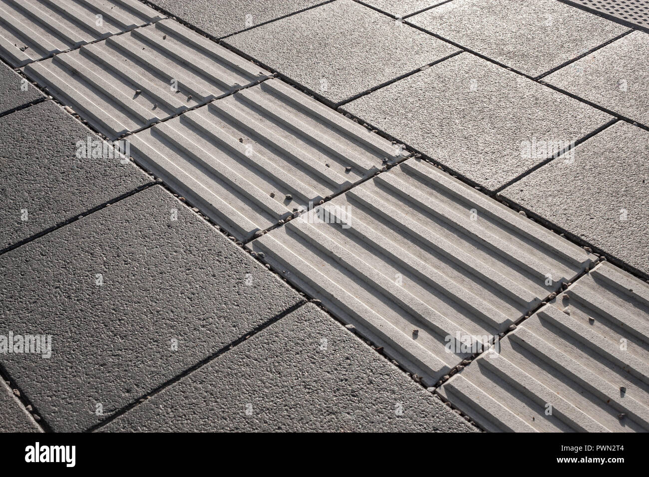 Line of hazard warning tactile paving along the edge of platform at the train station. Tactile paving assists visually impaired pedestrians - Stock Image