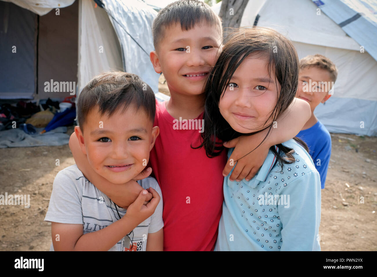 Refugee children from Syria and Afghanistan in front of the tents next to the camp MORIA CAMP for refugees. Island of Lesbos, Greece, May 2018 - Flüchtlingskinder aus Syrien und Afghanistan vor den Zelten  neben dem Lager MORIA CAMP für Flüchtlinge. Insel Lesbos, Griechenland, Mai 2018 - Stock Image