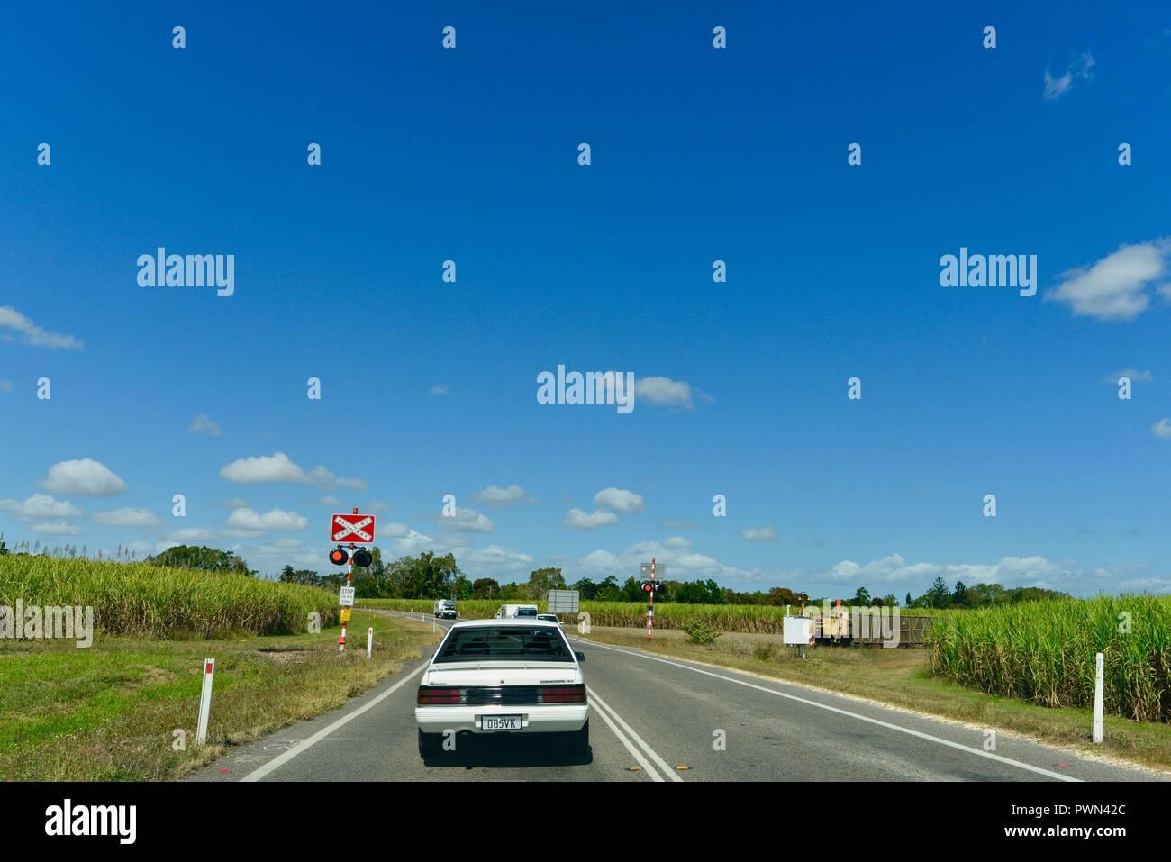 Sugarcane train crossing a road at a train crossing, Ingham, QLD, Australia Stock Photo