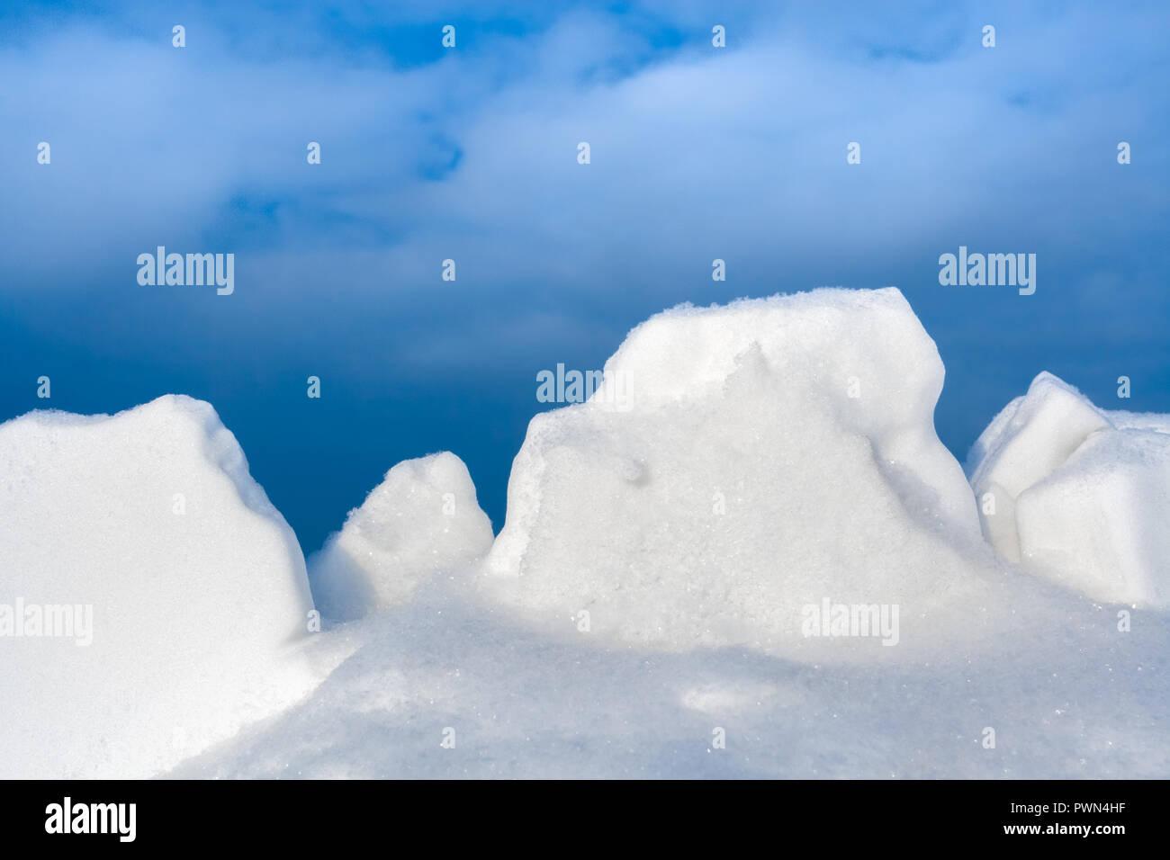 Close-up white snow lumps against blue sky.  - Stock Image