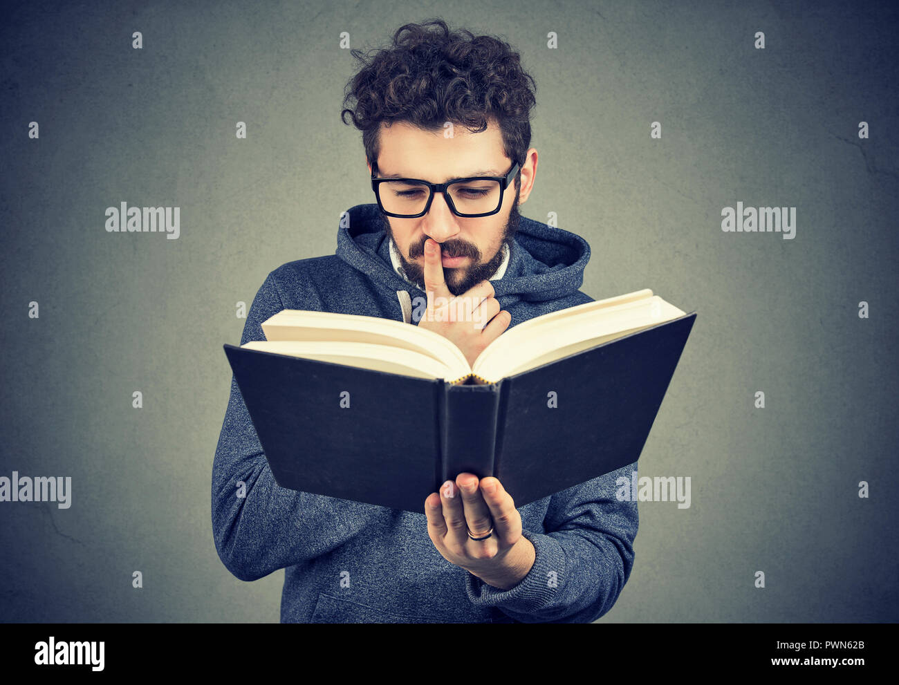 Young man in glasses looking confused while trying to read smart book on gray background - Stock Image