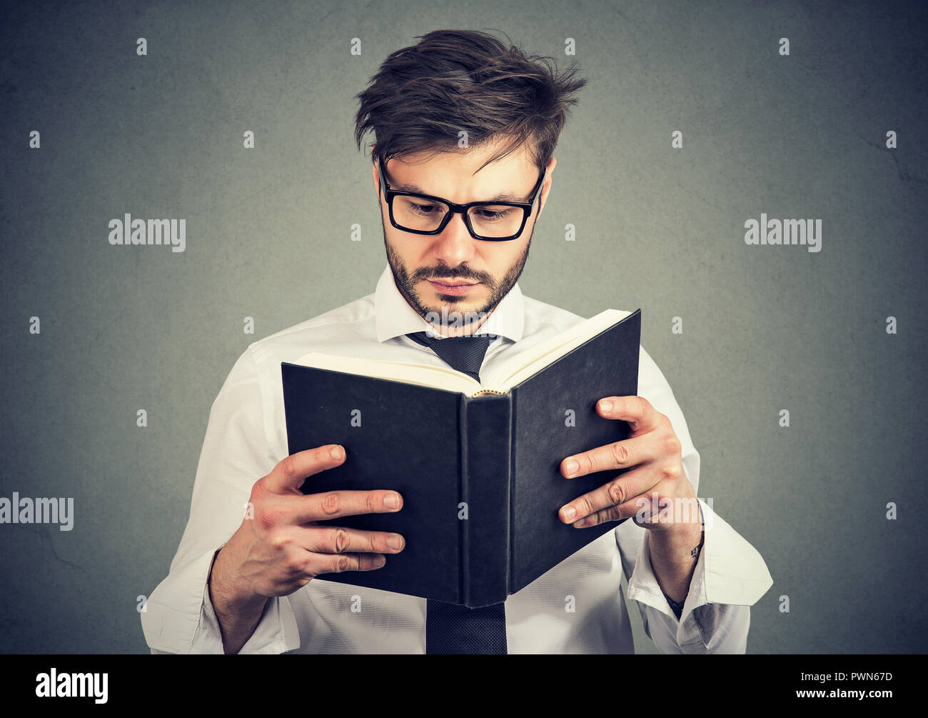 Young man in glasses reading a smart book on gray background - Stock Image