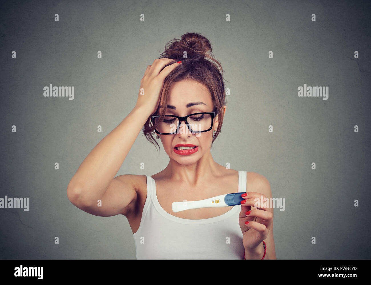 Portrait of a young shocked woman with positive pregnancy test Stock Photo