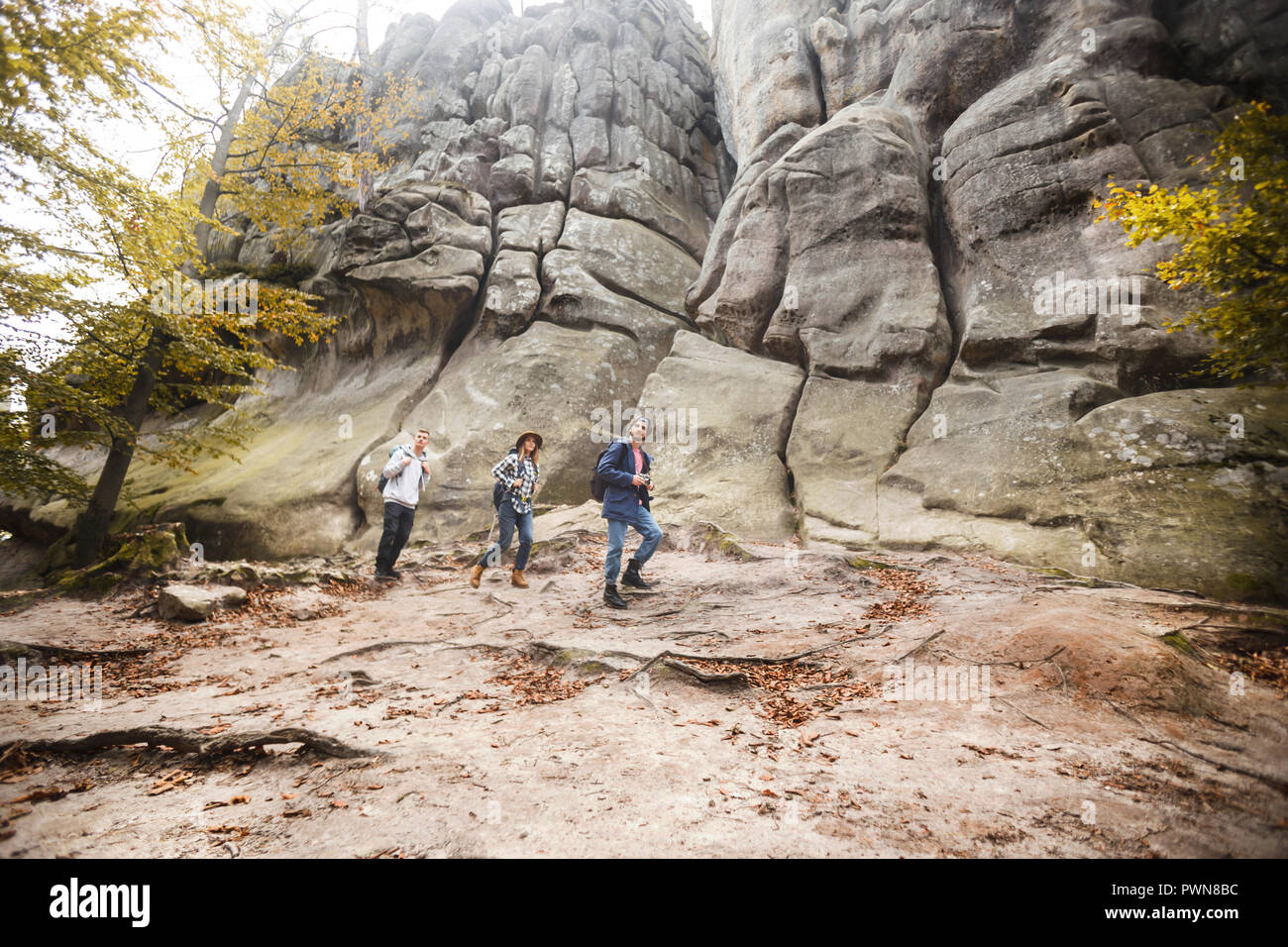Three young travellers with backpacks hiking in the beautiful rocks, travelling concept Stock Photo