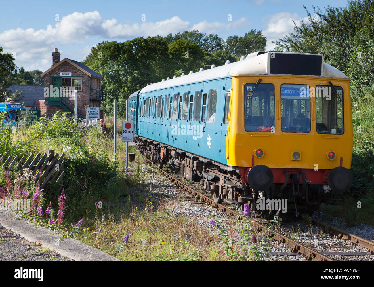 A diesel multiple unit passenger train leaving Wensleydale Railway's Bedale station passing the level crossing and signal box - Stock Image