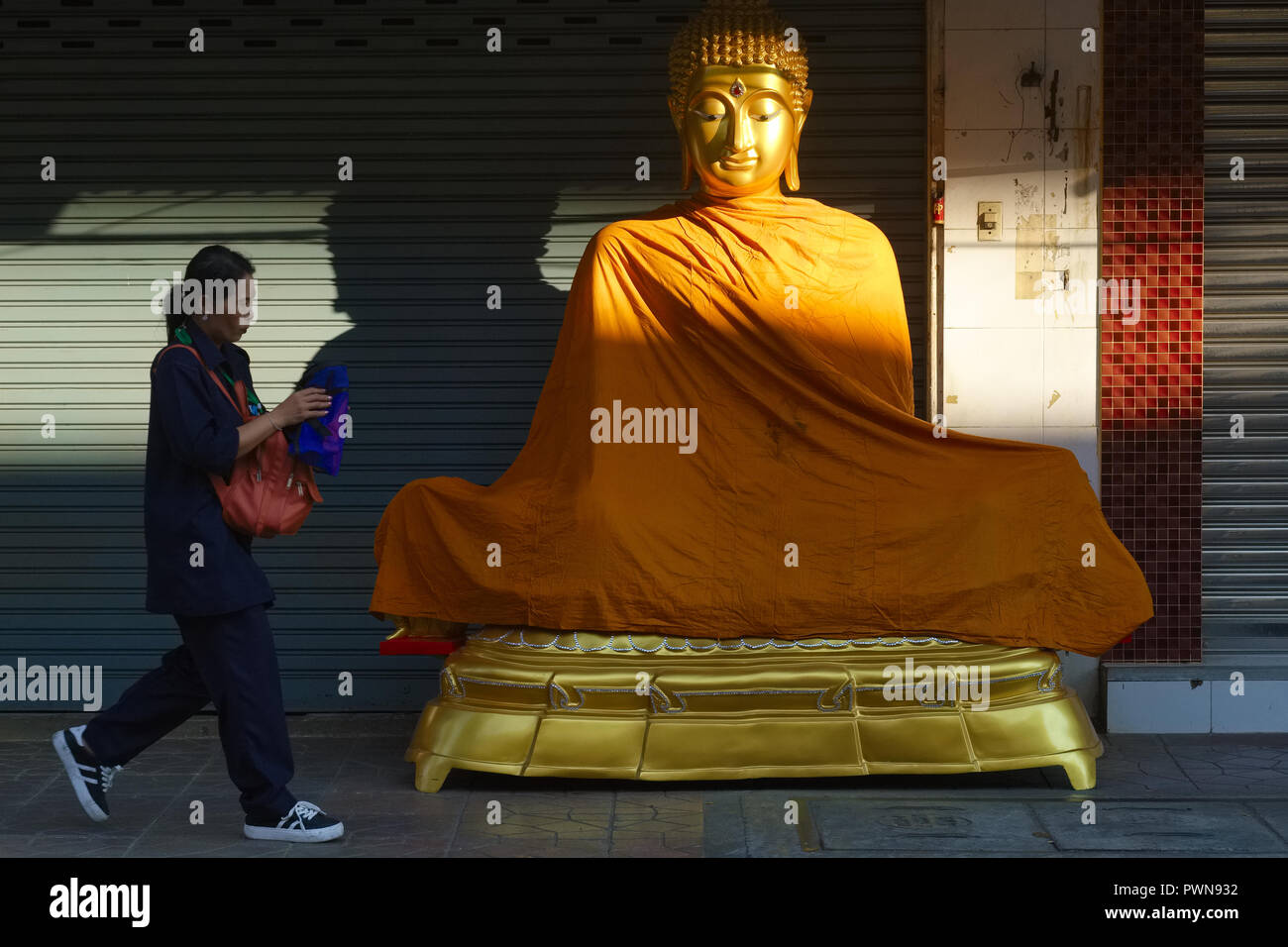 An early morning walker passing a Buddha statue placed in front of a shop for religious artifacts, in Bamrung Muang Road, Bangkok, Thailand - Stock Image