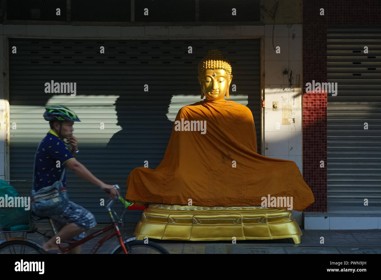 An early morning cyclist passing a Buddha statue placed in front of a shop for religious artifacts, in Bamrung Muang Road, Bangkok, Thailand - Stock Image
