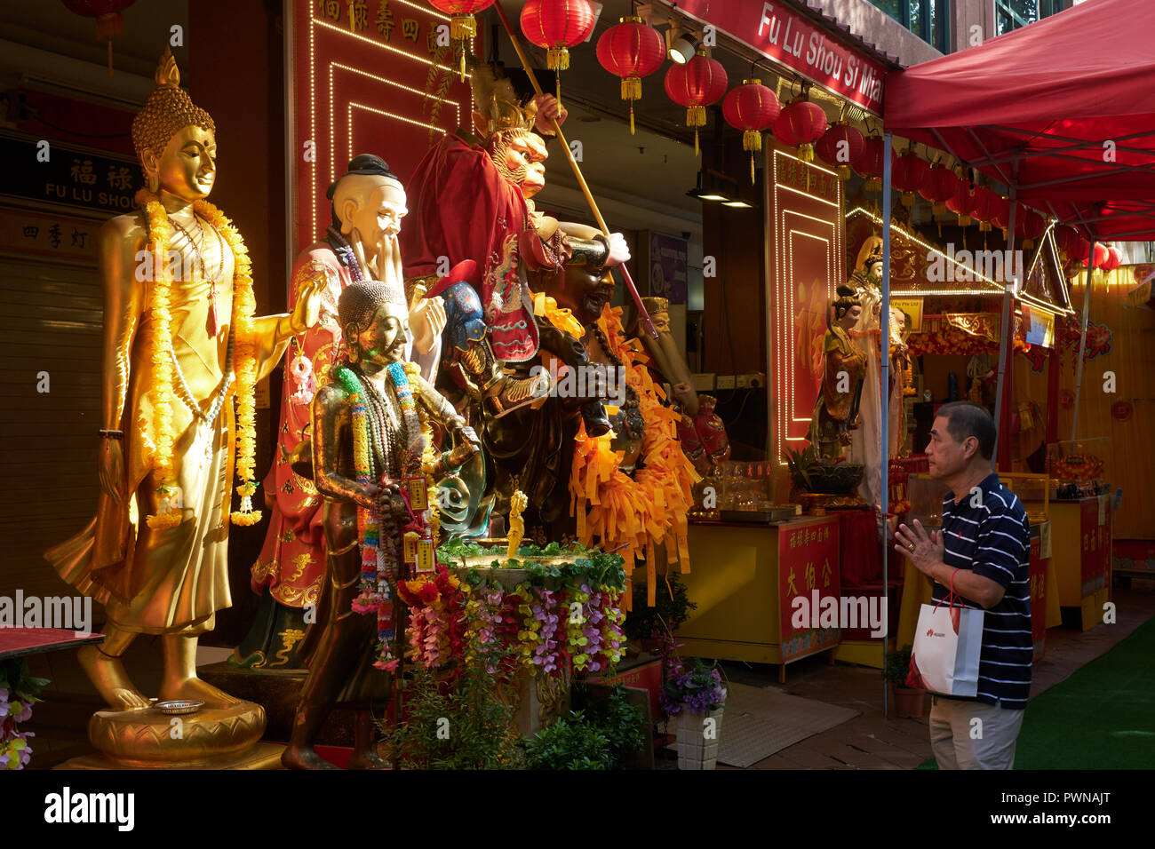 Taoist and Buddhist street shrines with multiple deities in Waterloo Street, Bugis area, Singapore, attracting a constant flow of worshippers - Stock Image