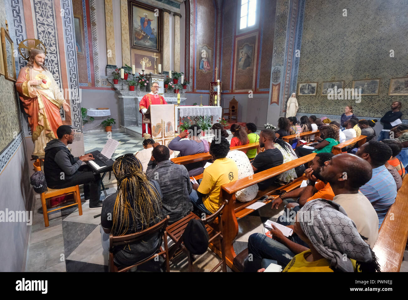 Church service for Refugees in the Assumption of Virgin Mary Church in the island's capital, Mytilini, Lesvos Island, Greece, May 2018 - Stock Image
