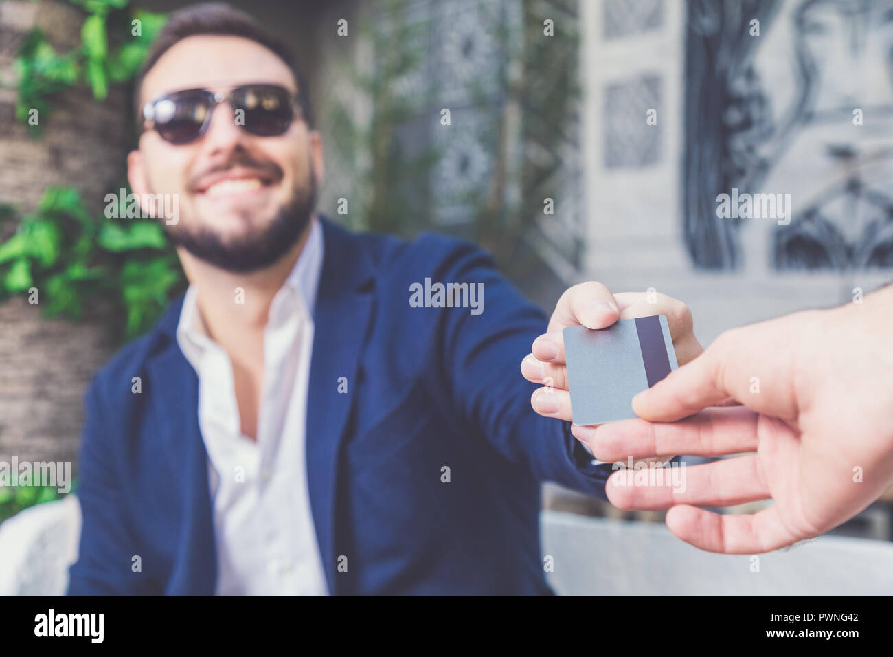 successful handsome businessman paying bill with credit card in cafe stock image