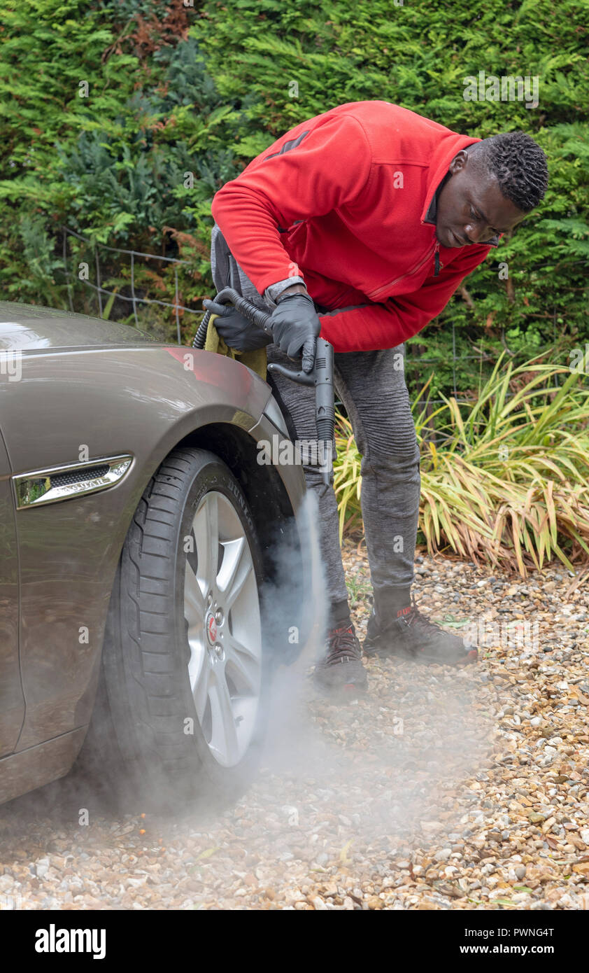Man steam cleaning a luxury car on a home visiting valet service, England UK - Stock Image