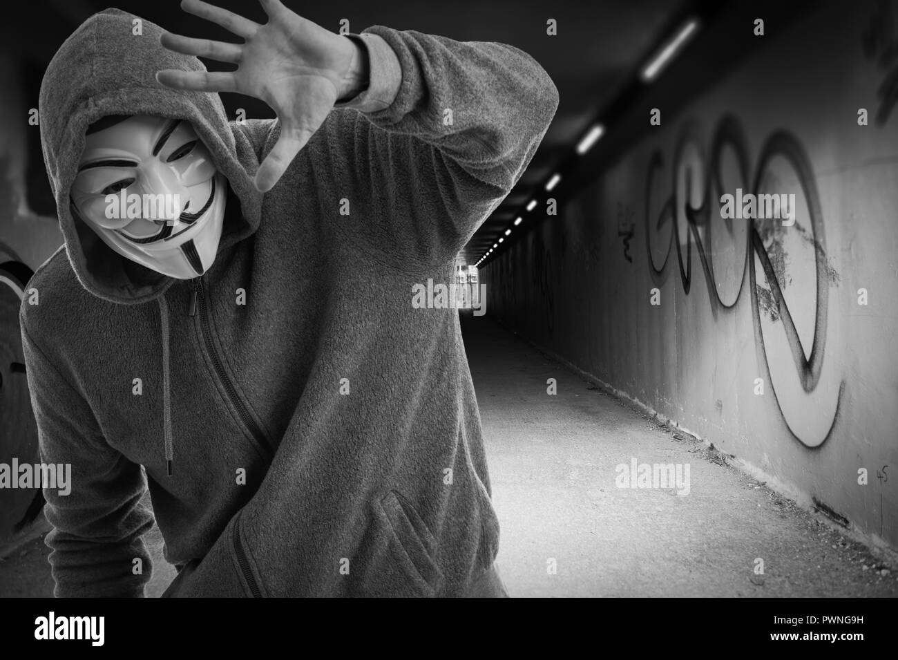 man wearing a Guy Fawkes mask at the entrance to a tummel, anonymous. - Stock Image