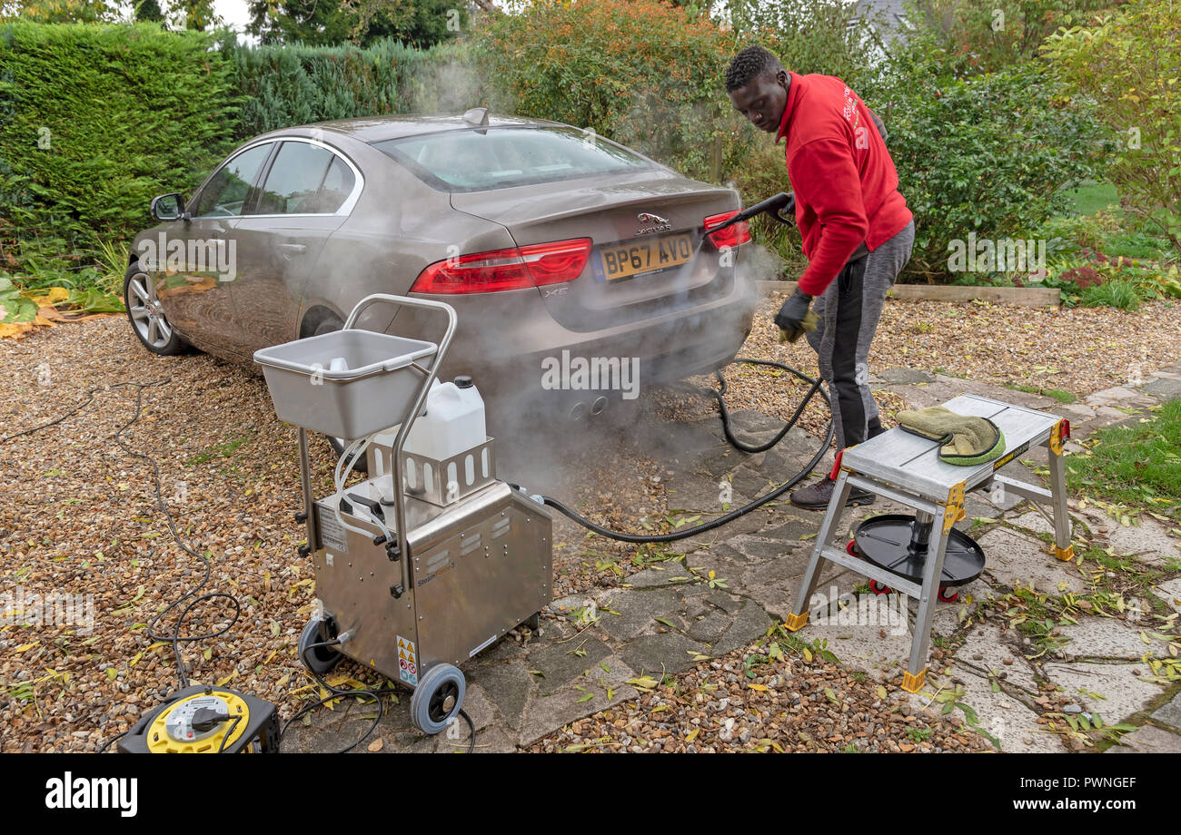 Man using a mobile steam cleaning machine to clean a luxury car on a home visiting valet service, England UK - Stock Image
