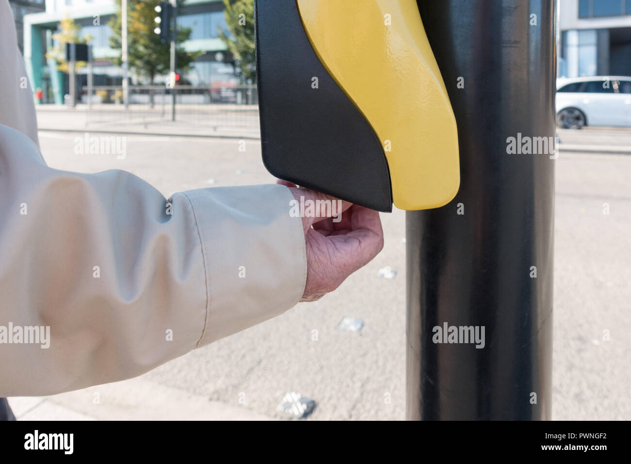 visually impaired blind elderly man using pedestrian road crossing rotating cone aid on underside of push button control box, Dundee, Scotland, UK - Stock Image
