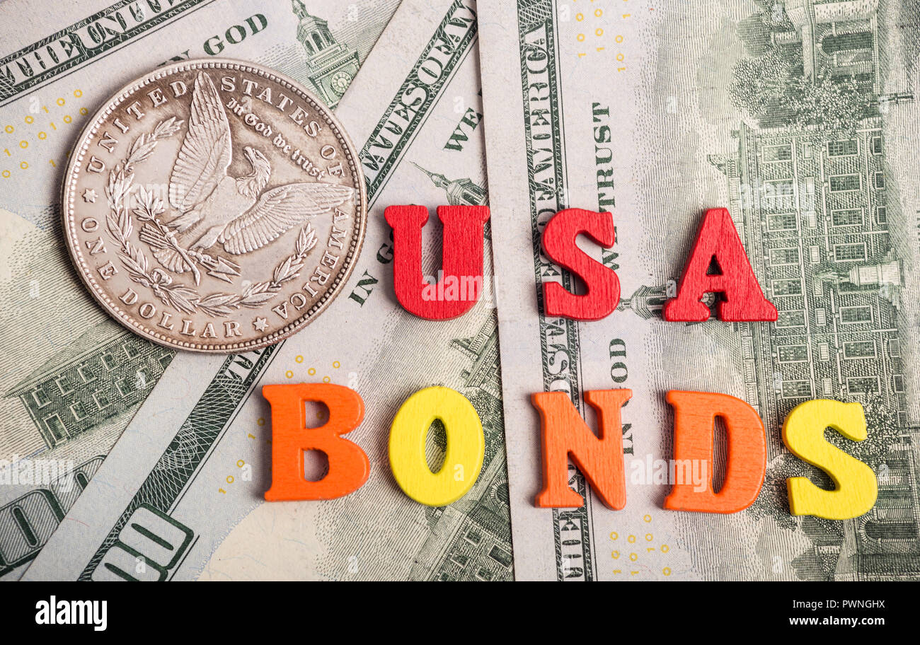 Bonds investment at wooden letters on US Dollar bills - Stock Image