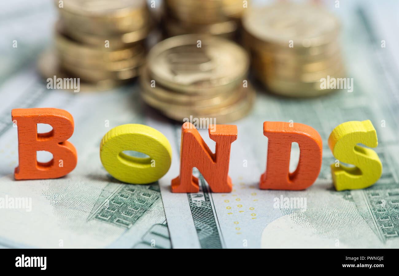 Bonds investment at wooden letters on US Dollar bills and golden coins - Stock Image