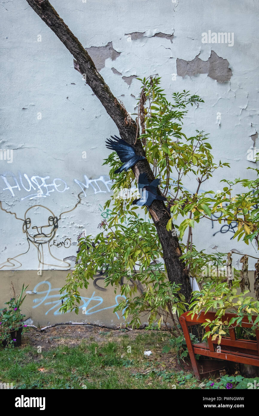 Berlin, Mitte. Painted paper birds in tree in Children's play area between buildings with weathered old wall Stock Photo