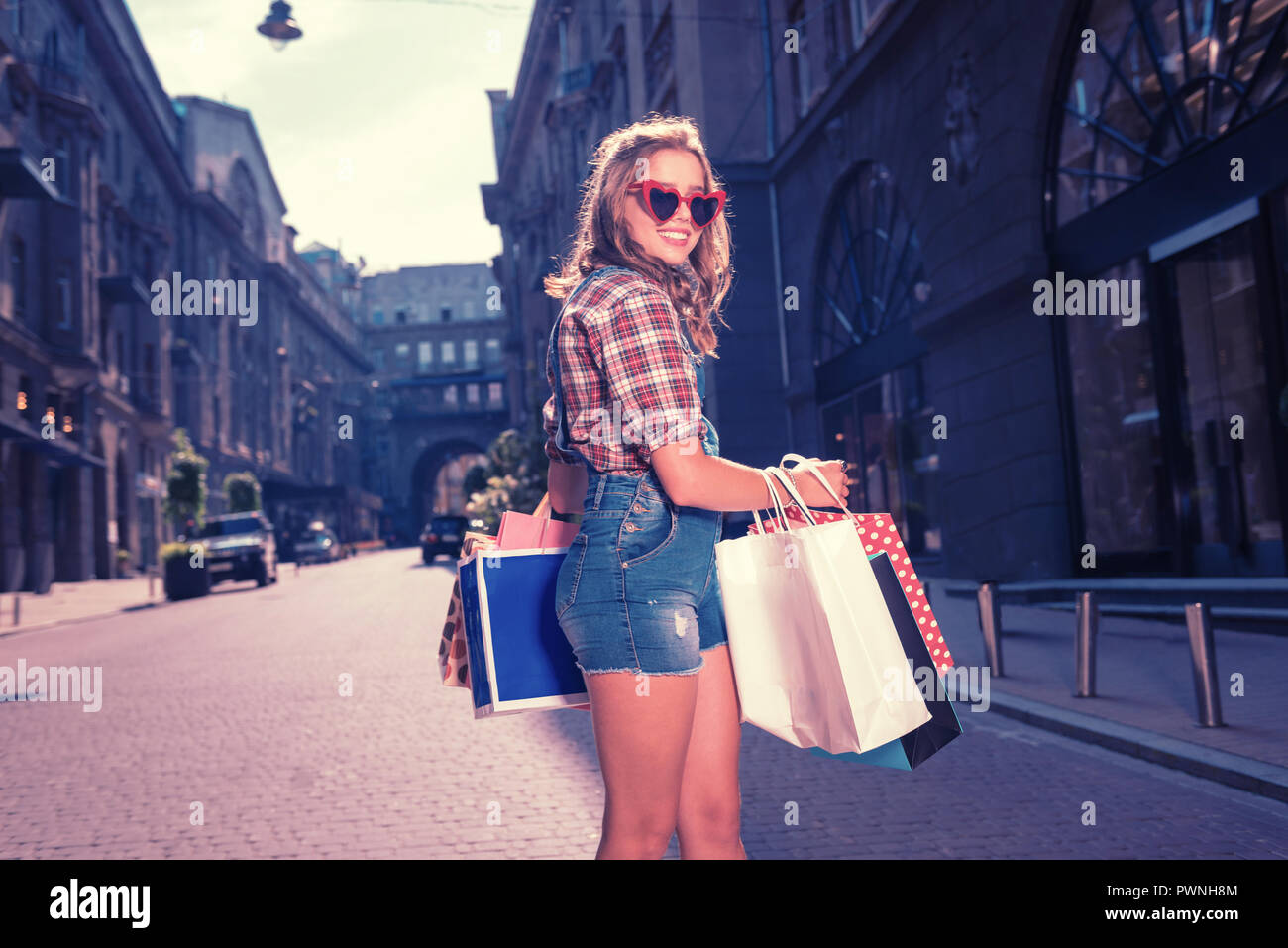 Stylish woman wearing squared shirt and denim jumpsuit holding shopping bags - Stock Image