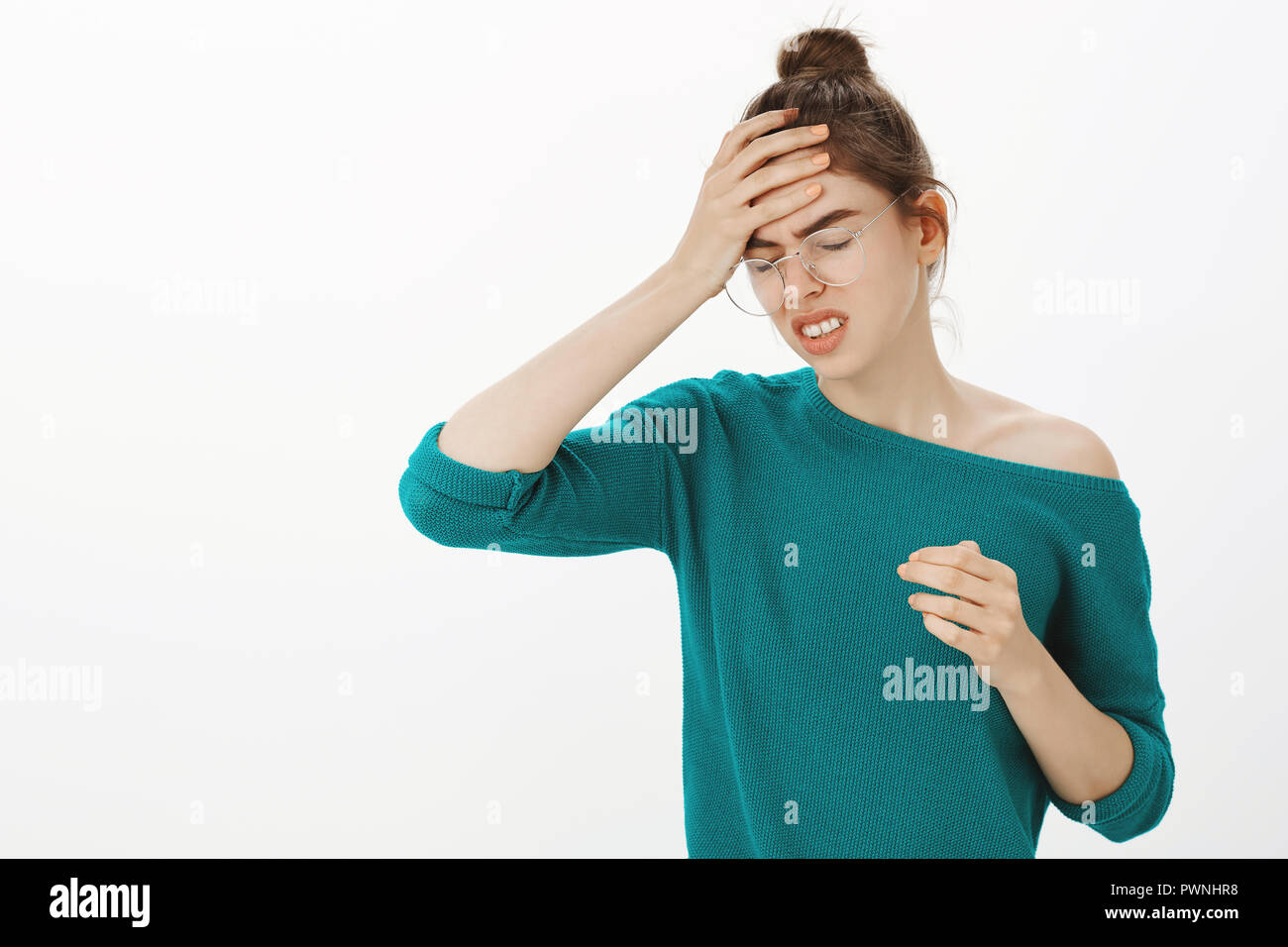 Bring me painkillers, head killing me. Intense displeased cute businesswoman in glasses and loose sweater, frowning, clenching teeth and holding hand on forehead, feeling headache or migraine - Stock Image