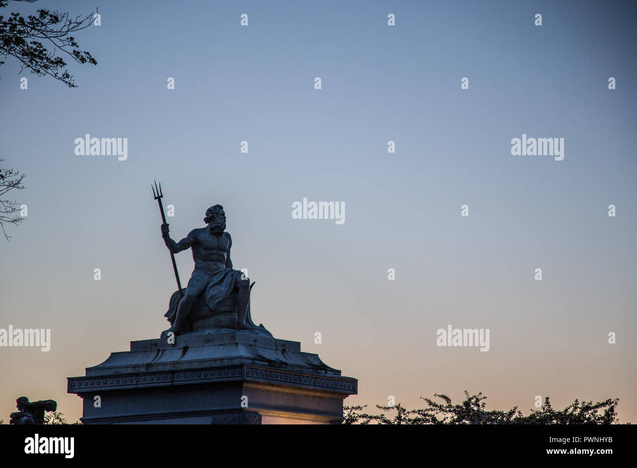 Statue of the Greek god of the sea, Poseidon, located in the port of Copenhagen during sunset (blue hour) - Stock Image