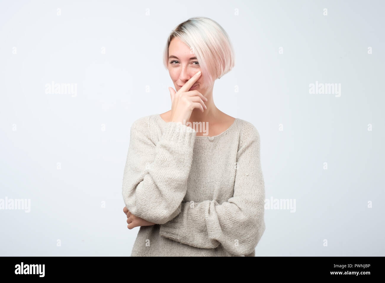 Cunning beautiful woman with dyed short hair looking holding hand under chin intending to realize tricky plan. - Stock Image