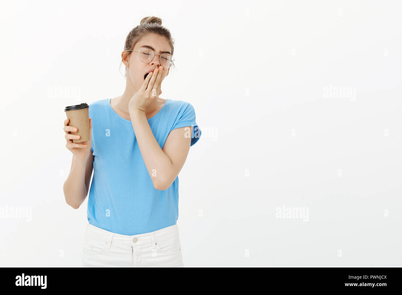 Tied of working hard all day. Portrait of exhausted good-looking female in glasses and bun hairstyle, yawning and covering opened mouth with palm, closing eyes and holding cup of coffee in morning - Stock Image