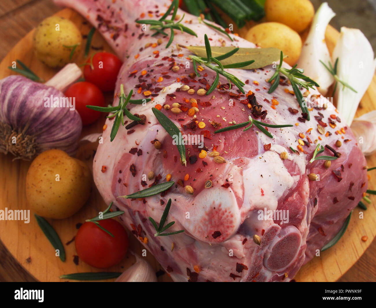 Fresh and raw meat. Leg of lamb on wood background - Stock Image