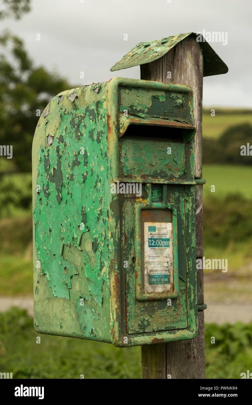 Old green Irish post box with peeling layers of green paint on wooden stake in the countryside. - Stock Image