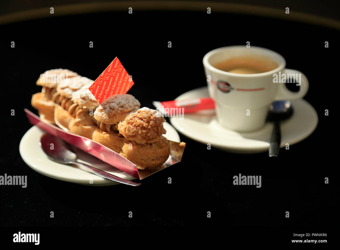 Paris Brest Patisserie and coffee on a black table. - Stock Image