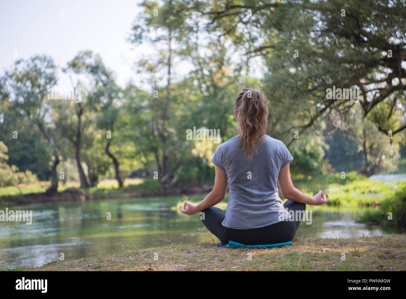 Healthy Woman Relaxing While Meditating And Doing Yoga Exercise In The Beautiful Nature On The Bank Of The River Stock Photo Alamy