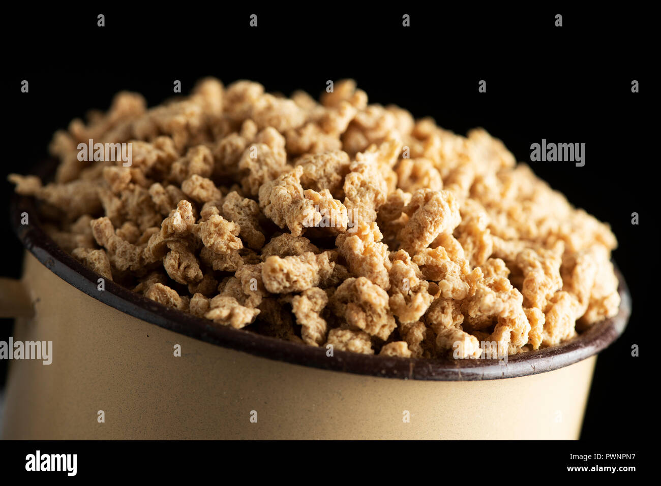closeup of an old beige enamelware pot full of chunks of textured soy protein, against a black background - Stock Image