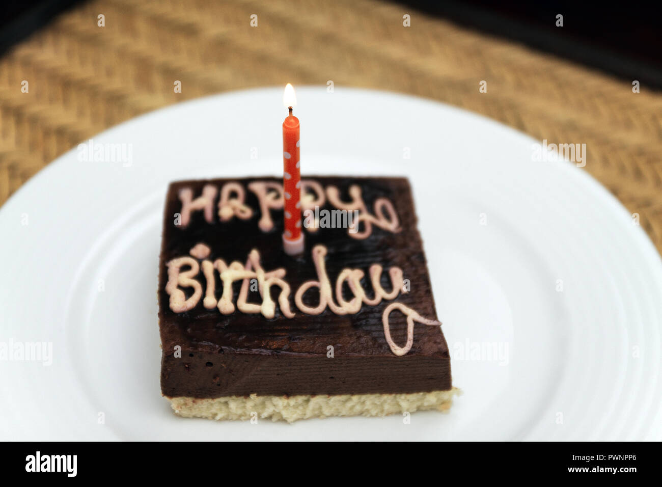 Small Square Festive Chocolate Cake With The Inscription Happy Birthday And One Candle On A White Plate