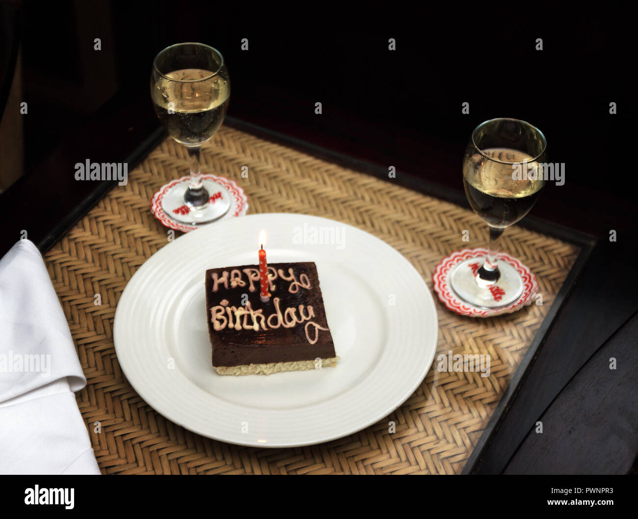 A Small Square Chocolate Birthday Cake With The Inscription Happy And One Candle On White Plate Next To Two Glasses Of Wine