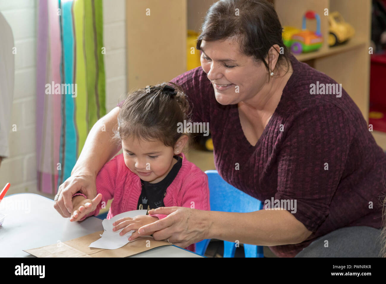 Alpine, Texas - Mari Rodriguez helps children with an art project in the two-year-olds classroom at the Alpine Community Center. The Center is a missi - Stock Image