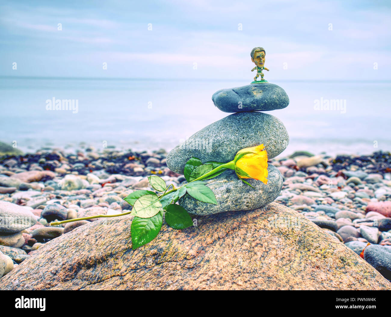 Pyramid of sea stones on pebbles with yellow rose. Chidren toy of football player. Moody walk at sea shore. Seascape - Stock Image