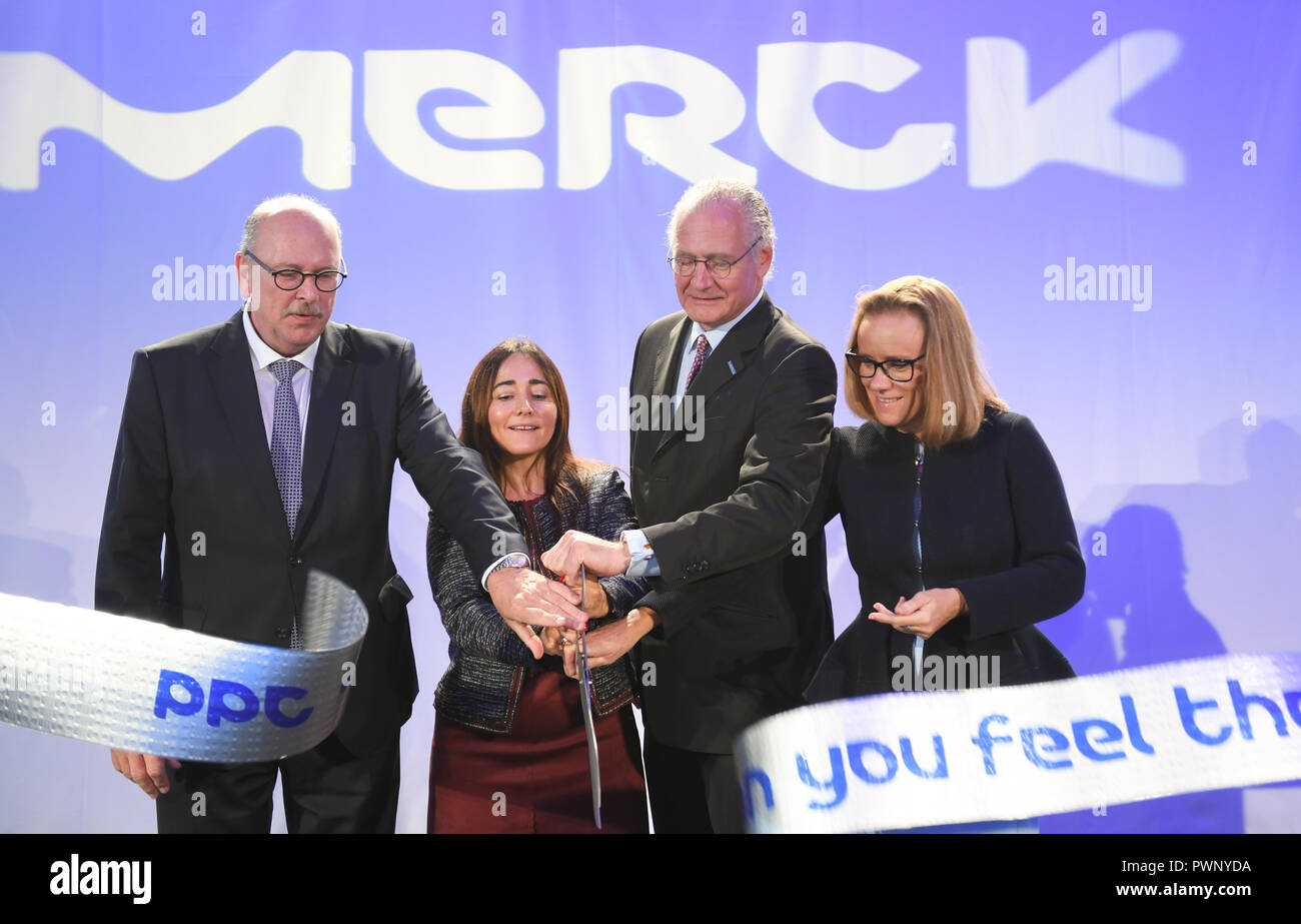 Darmstadt, Hessen. 17th Oct, 2018. Stefan Grüttner (CDU, l-r), Minister of Health of the State of Hesse, Teresa Rodo, Stefan Oschmann, Chairman of the Executive Board of Merck KGaA, and Belen Garijo, Member of the Executive Board of Merck, cut a blister band at the opening of the new pharmaceutical packaging center at the headquarters of the Darmstadt chemical and pharmaceutical company. Merck has invested around 63 million euros in its state-of-the-art facility. The packaging centre has a capacity of more than 210 million pharmaceutical packages. Credit: Arne Dedert/dpa/Alamy Live News Stock Photo