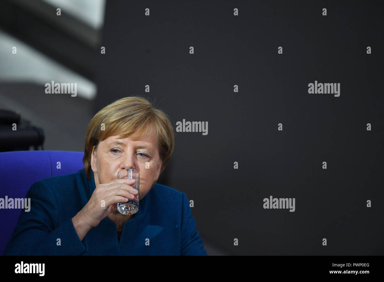 Berlin, Germany. 17th Oct, 2018. Federal Chancellor Angela Merkel (CDU) sits in the government bench at the plenary session in the German Bundestag after her government declaration on the EU summit in Brussels and drinks from a glass. The 57th session of the 19th legislature will focus on European policy. Photo: Bernd Von Jutrczenka/dpa Credit: dpa picture alliance/Alamy Live News - Stock Image