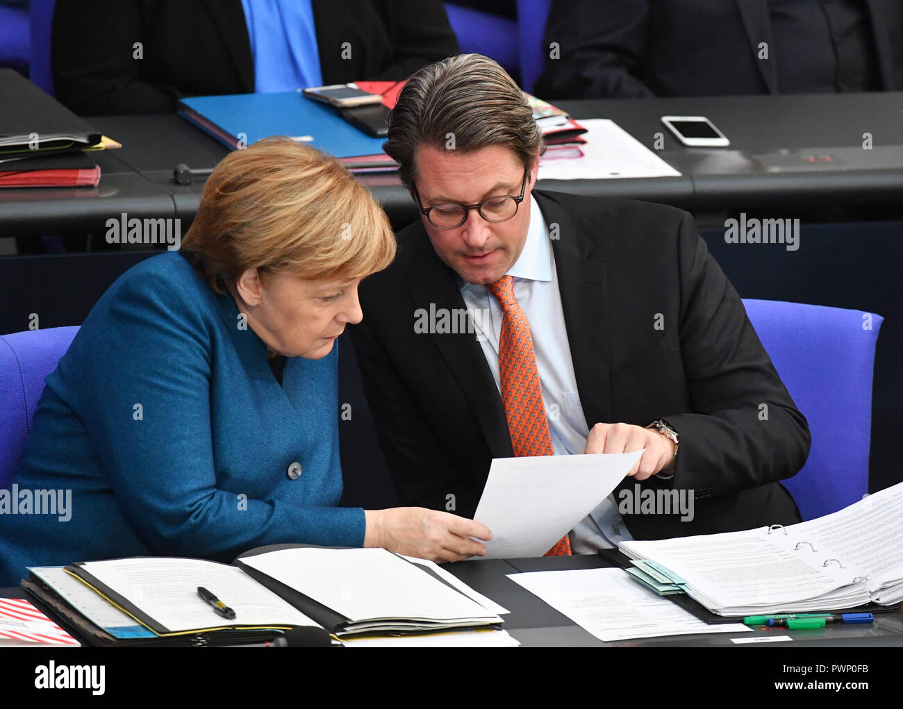 Berlin, Germany. 17th Oct, 2018. Federal Chancellor Angela Merkel (CDU) talks to Transport Minister Andreas Scheuer (CSU) at the plenary session of the German Bundestag after her government statement on the EU summit in Brussels at the government bank. The 57th session of the 19th legislature will focus on European policy. Photo: Bernd Von Jutrczenka/dpa Credit: dpa picture alliance/Alamy Live News - Stock Image