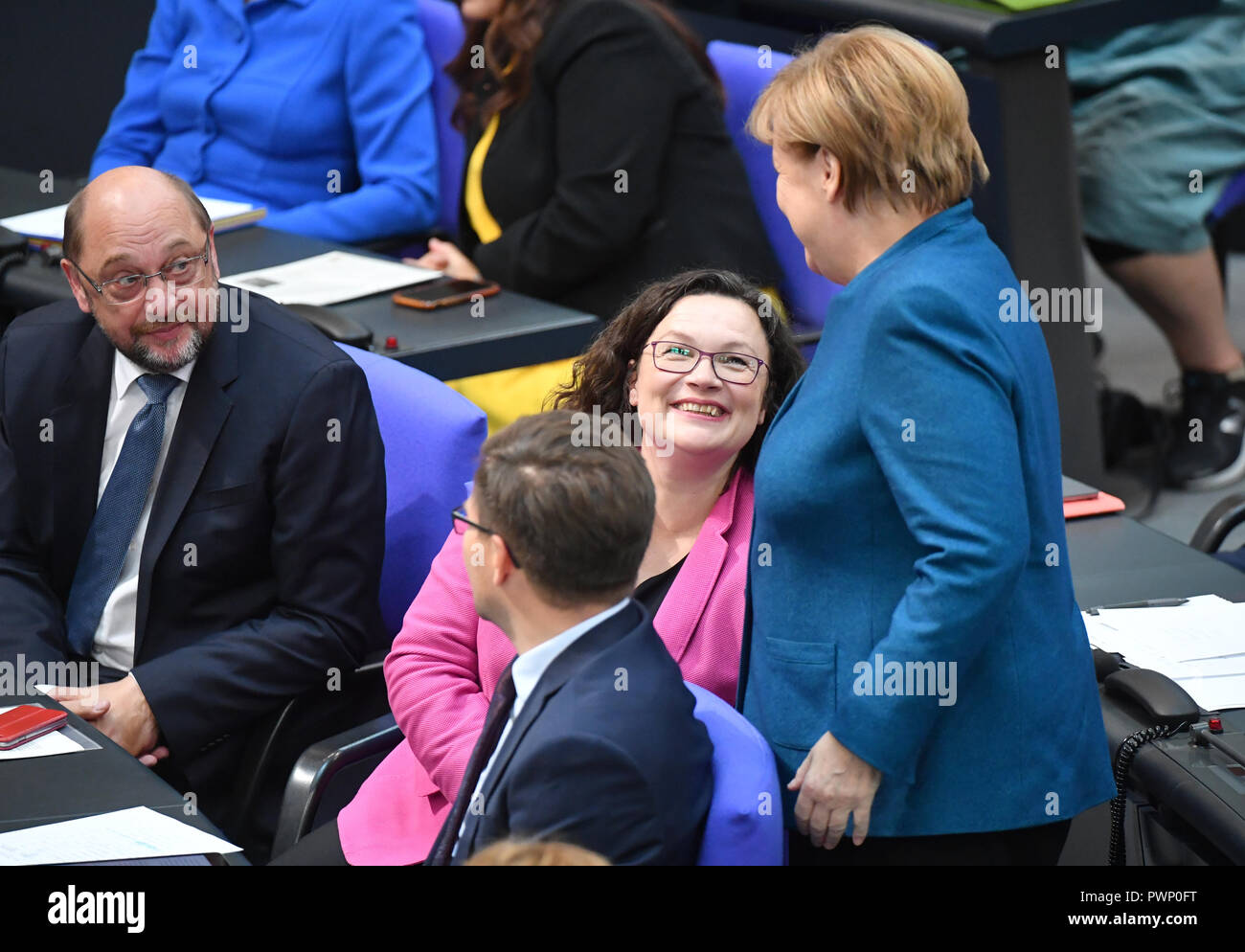 Berlin, Germany. 17th Oct, 2018. Chancellor Angela Merkel (CDU, r-l) talks to SPD Chairwomen Andrea Nahles and Martin Schulz (SPD) at the plenary session of the German Bundestag following their government declaration on the EU summit in Brussels. The 57th session of the 19th legislature will focus on European policy. Photo: Bernd Von Jutrczenka/dpa Credit: dpa picture alliance/Alamy Live News - Stock Image