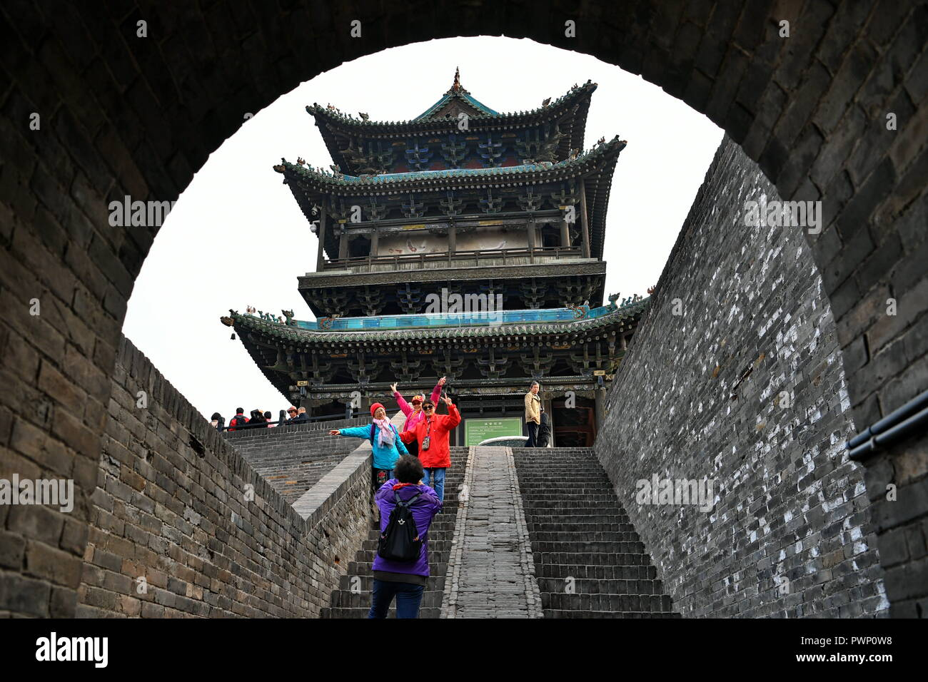 (181017) -- PINGYAO, Oct. 17, 2018 (Xinhua) -- Tourists visit the ancient walled city of Pingyao in Jinzhong, north China's Shanxi Province, on Oct. 17, 2018. The ancient walled city of Pingyao was built in the 14th century, and was named a UNESCO world heritage in 1997, as 'an exceptionally well-preserved example of a traditional Han Chinese city.' The city boomed in the 19th century as China's financial center, as Shanxi merchants expanded their businesses across the country. Now, the well-preserved compounds of these affluent merchants and some emerging modern elements like souvenir shops, - Stock Image